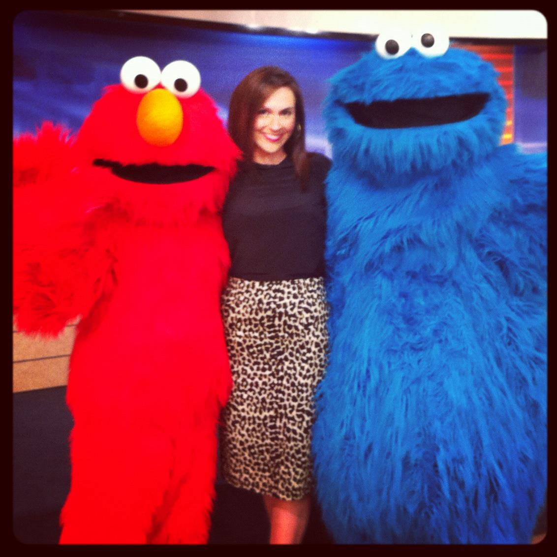 Ashley poses with Elmo and Cookie Monster during a commercial break.