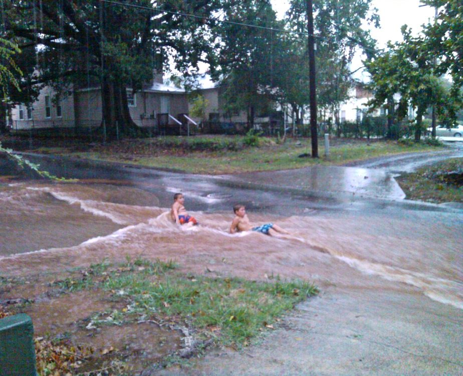 Neighbor boys using K Street as a water slide after lightening causes a water pipe to burst