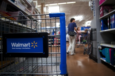 Interior of Walmart store - close-up of shopping cart on aisle.