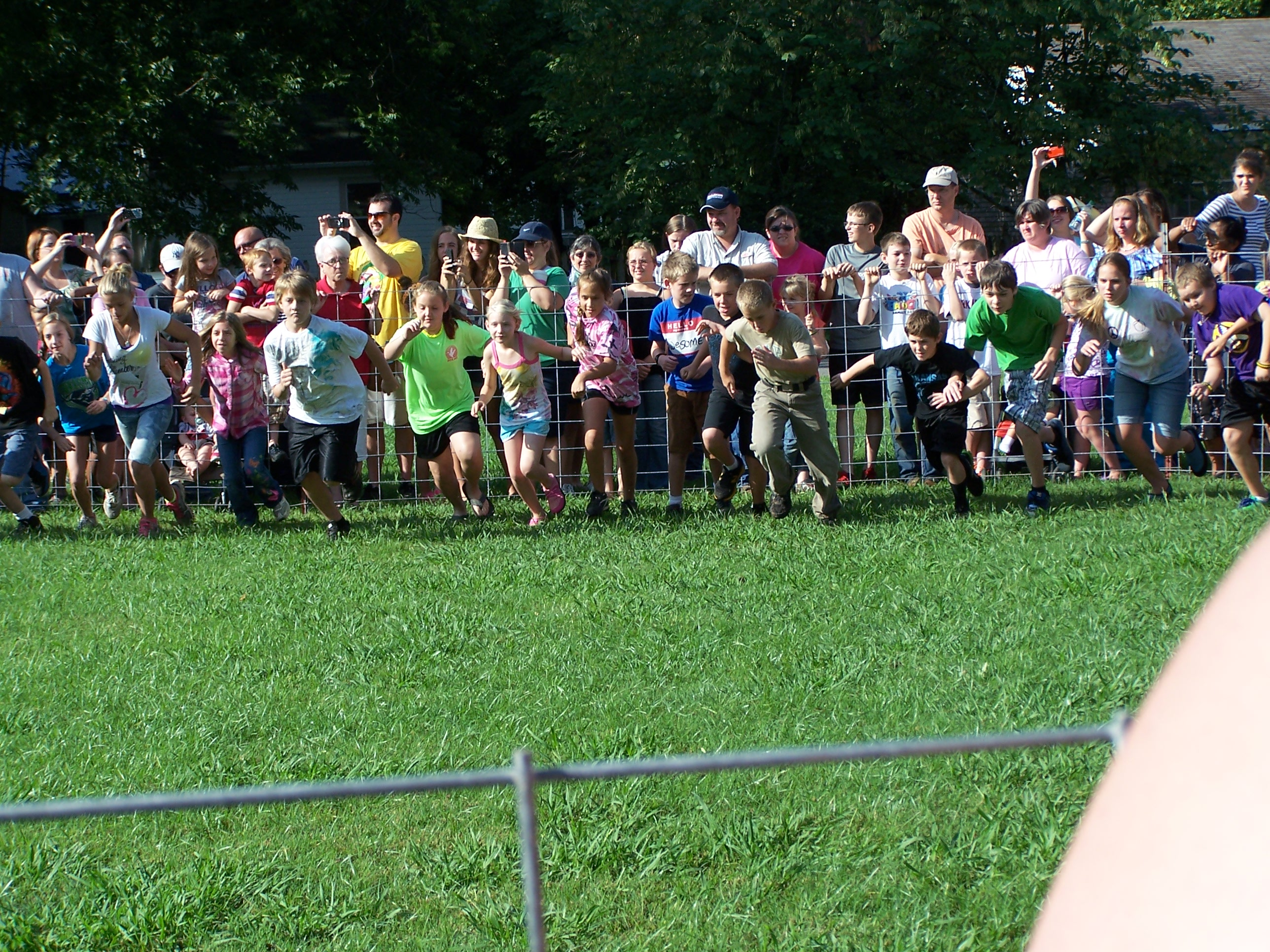 Kids haveing fun chaseing a pig took by Marilyn Cowell Clarksville