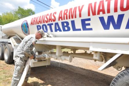 Connecting the line. Staff Sgt. Brad Broadstock, of the Arkansas National Guard, connects a hose to begin filling a 5,000 gallon water tanker during a water hauling mission on July 11, 2012.