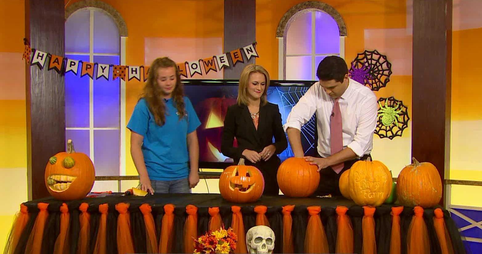 Joe digs out the insides of a pumpkin.