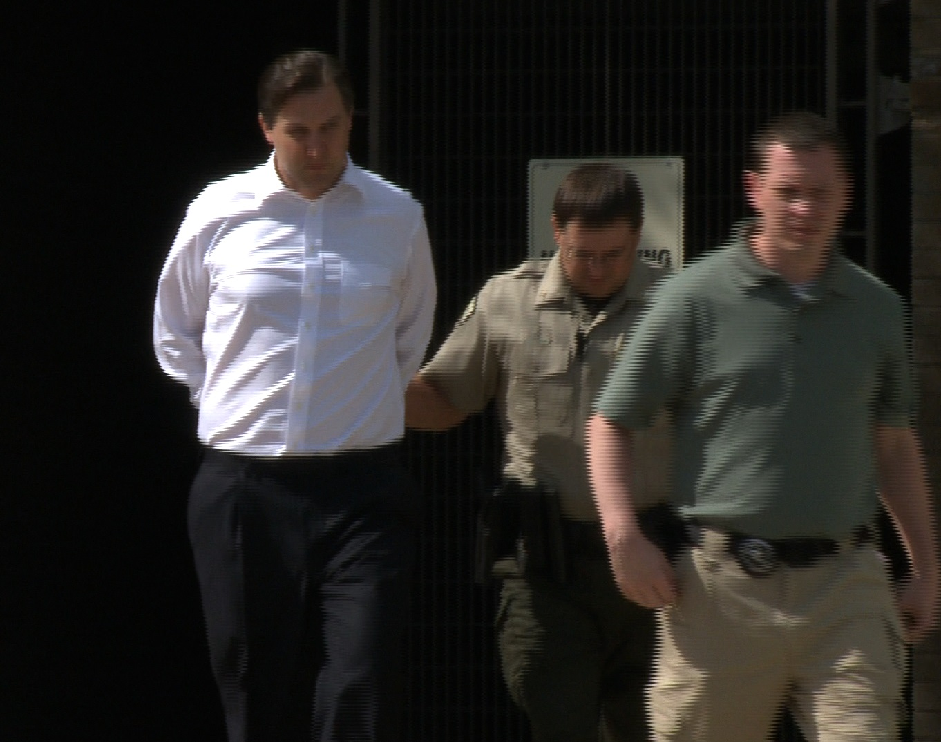 Barber being led away from federal court in handcuffs before being transferred to the Washington County Detention Center.