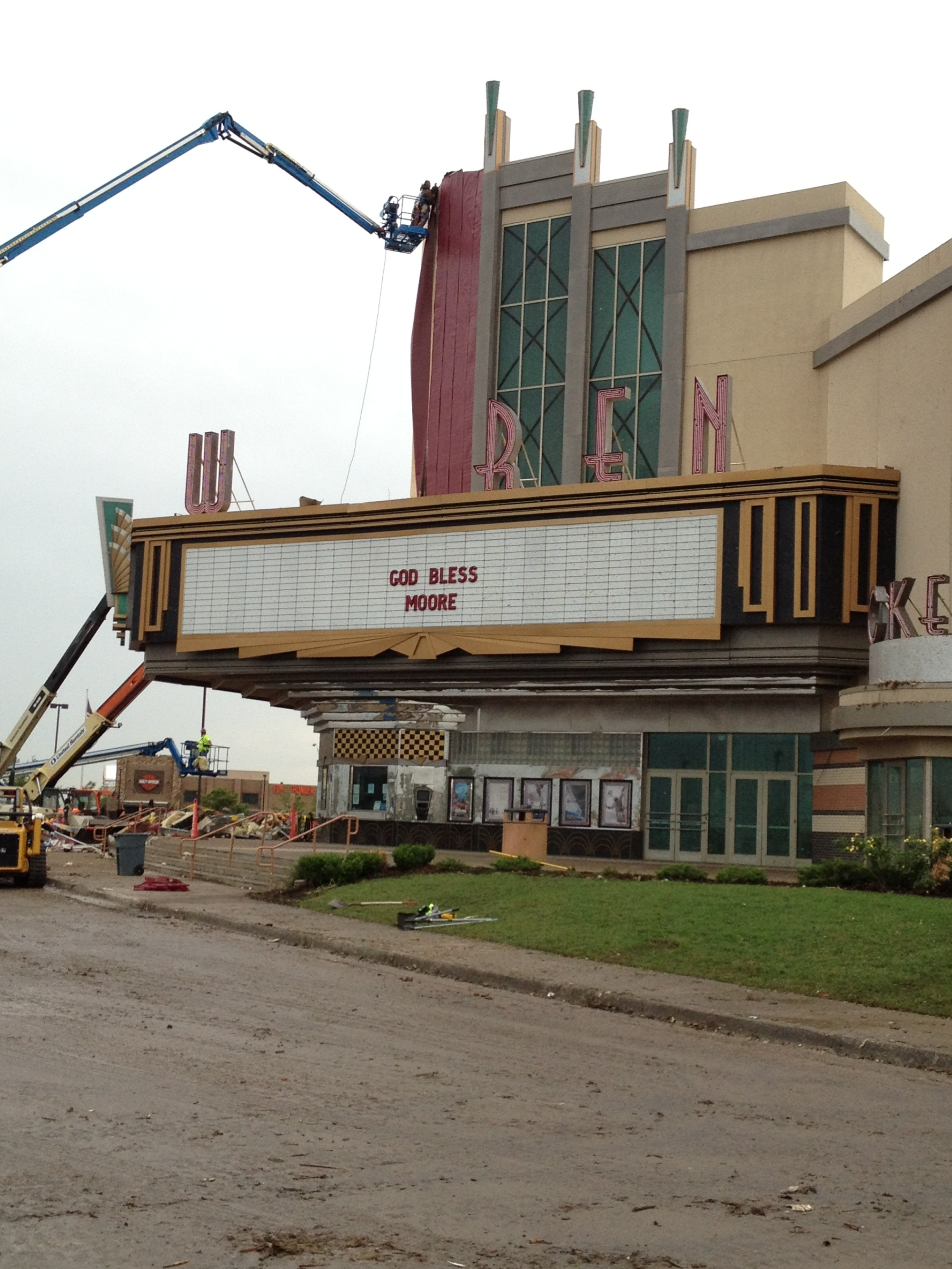 "As crews work to clean up the Moore Warren movie theater, a new message on the marquee, ""God Bless Moore."""
