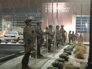 Snow falling on National Guard standing outside of Ferguson Police Department.