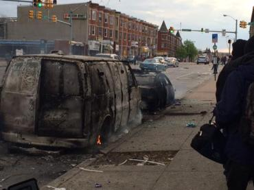 A police car and van burned on the streets of Baltimore
