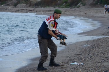 "Authorities in Bodrum, Turkey, stand near the body of a child who washed ashore on Wednesday, September 2. The child was one of 12 refugees who drowned during a failed attempt to sail to the Greek island of Kos. This photo has been shared widely around the world, often with a Turkish hashtag that means ""Flotsam of Humanity."""
