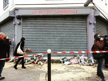 A woman lays flowers at the scene of the Paris shooting of Le Petit Cambodge restaurant. Parisians wandering around in shock, looking at the bullet holes in the windows.