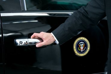 A U.S. Secret Service agent waits to open the motorcade door as President Barack Obama arrives at the Uptown Theater in Kansas City, Mo., July 30, 2014.