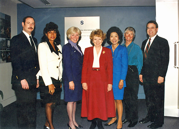 "Challenger Center founding family members (left to right): Charles Resnik, brother of astronaut Judy Resnik; Cheryl McNair, wife of astronaut Ronald McNair; Jane Smith Wolcott, wife of Challenger pilot Michael Smith; June Scobee Rodgers, wife of commander Francis ""Dick"" Scobee; Lorna Onizuka, wife of astronaut Ellison Onizuka; Maria Jarvis-Tinsley, wife of payload specialist Gregory Jarvis; and Steven McAuliffe, husband of high school teacher/payload specialist Christa McAuliffe. Courtesy Challenger Center"