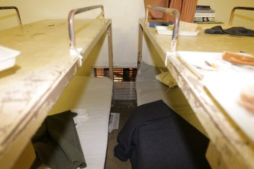 Cut steel screen where inmates made access to plumbing tunnel from tank in California jail escape.