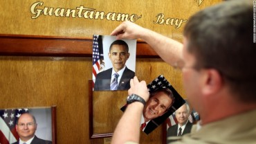 GUANTANAMO BAY, CUBA -- U.S. Navy Chief Petty Officer Bill Mesta replaces an official picture of outgoing President George W. Bush with that of newly- sworn-in U.S. President Barack Obama, in the lobby of the headquarters of the U.S. Naval Base January 20, 2009 in Guantanamo Bay, Cuba.  (Photo by Brennan Linsley-Pool/Getty Images) Bill Mesta