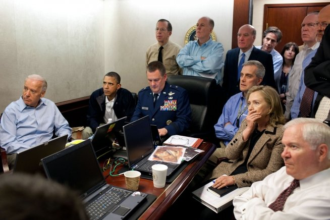 "President Barack Obama and Vice President Joe Biden, along with members of the national security team, receive an update on the mission against Osama bin Laden in the Situation Room of the White House, May 1, 2011. Seated, from left, are: Brigadier General Marshall B. ""Brad"" Webb, Assistant Commanding General, Joint Special Operations Command; Deputy National Security Advisor Denis McDonough; Secretary of State Hillary Rodham Clinton; and Secretary of Defense Robert Gates. Standing, from left, are: Admiral Mike Mullen, Chairman of the Joint Chiefs of Staff; National Security Advisor Tom Donilon; Chief of Staff Bill Daley; Tony Binken, National Security Advisor to the Vice President; Audrey Tomason Director for Counterterrorism; John Brennan, Assistant to the President for Homeland Security and Counterterrorism; and Director of National Intelligence James Clapper. Please note: a classified document seen in this photograph has been obscured."