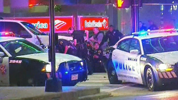 Officers huddle behind squad cars after a shooting at police protest in downtown Dallas, Thursday, July 7, 2016. KTVT Dallas