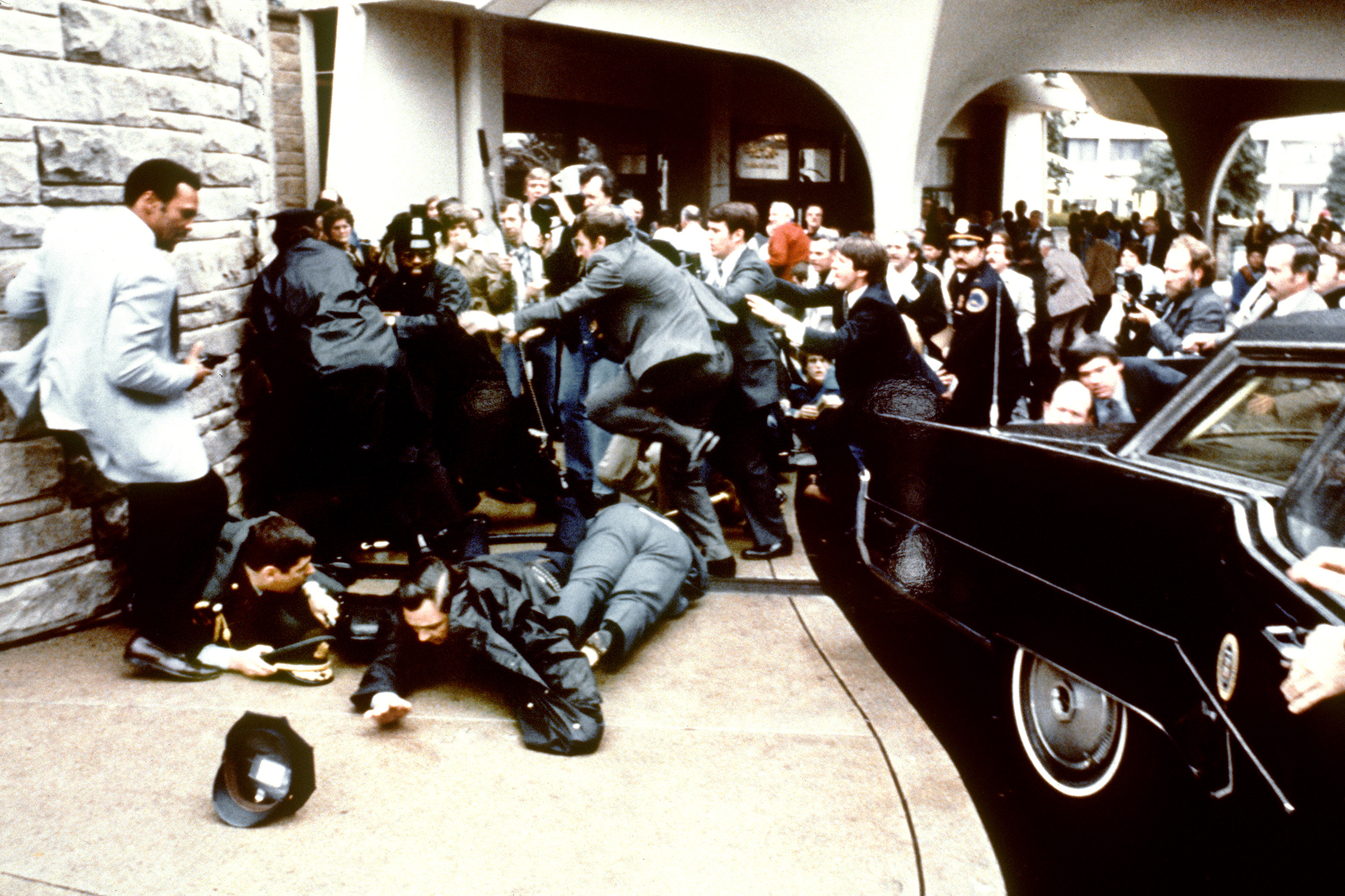 This photo taken by presidential photographer Mike Evens on March 30, 1981 shows police and Secret Service agents reacting during the assassination attempt on then US president Ronald Reagan, after a conference outside the Hilton Hotel in Washington, D.C.. Reagan was hit by one of six shots fired by John Hinckley, who also seriously injured press secretary James Brady (just behind the car). Reagan was hit in the chest and was hospitalized for 12 days. Hinckley was aquitted 21 June 1982 after a jury found him mentally unstable. Photo credit: MIKE EVENS/AFP/Getty Images
