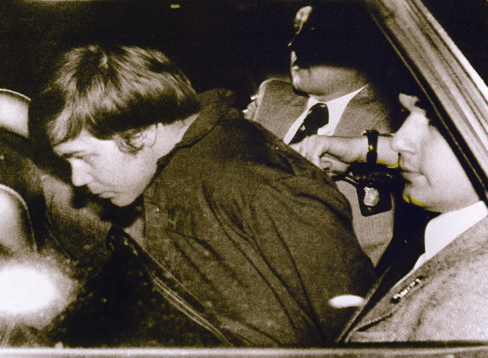 This 30 March 1981 file photo shows John Hinckley Jr. (L) escorted by police in Washington, DC, following his arrest after shooting and seriously wounding then US president Ronald Reagan.  A federal judge ruled 17 December 2003 Hinckley can make local visits with his family from St. Elizabeth's Hospital in Washington, DC, where he has been held.     AFP PHOTO/FILES   Photo credit AFP/Getty Images