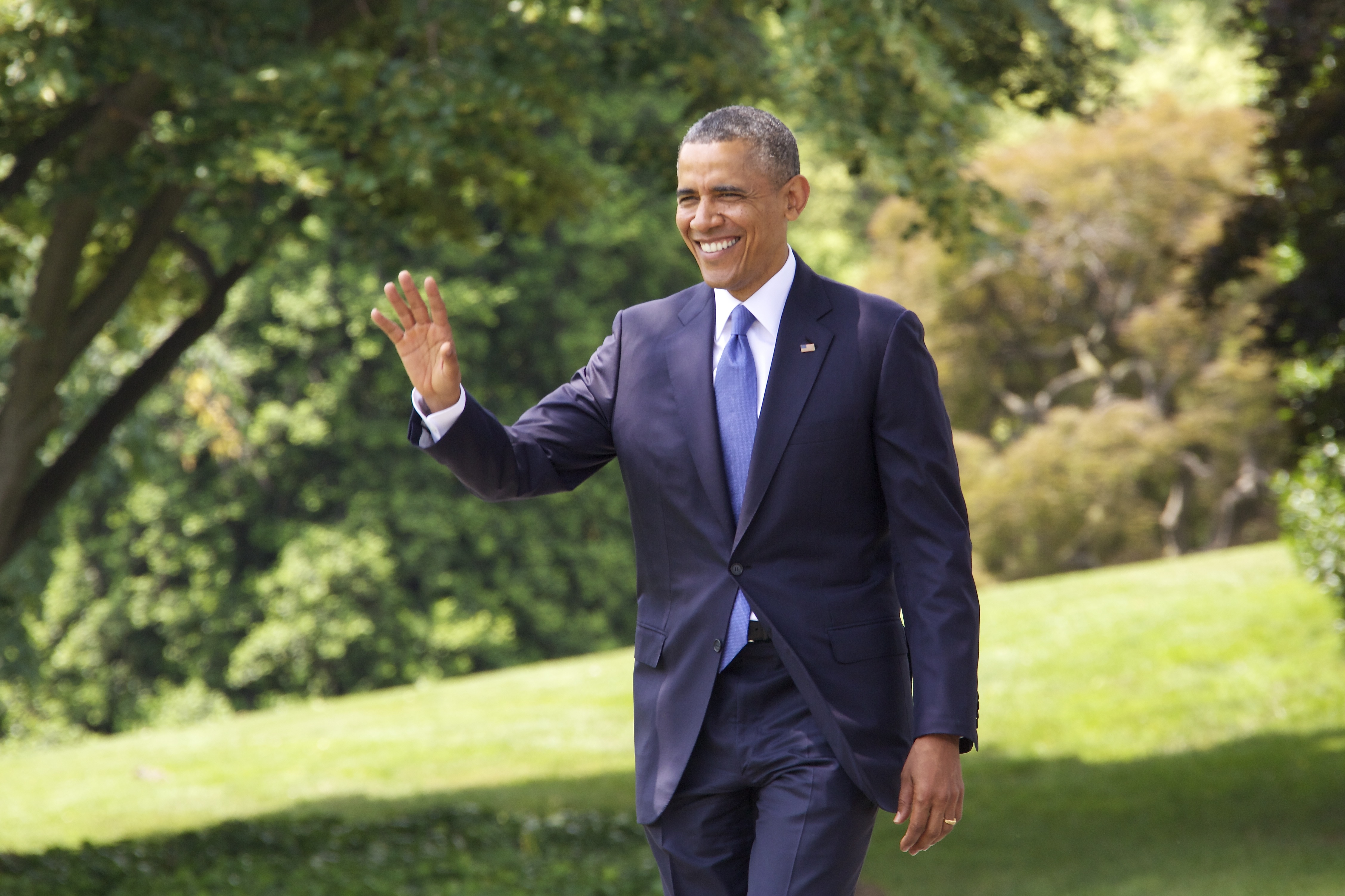 President Barack Obama waves as he walks on the White House lawn Friday, June 13, 2014.