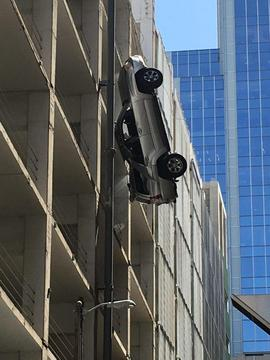 Slug: Car dangling off building Date Taken: Location: Austin, TX Mandatory Credit: Gary Clarke Source/URL: Gary Clarke Submitted by: bischofft@cbsnews.com - All Platforms In Perpetuity? Yes - Newspath or Affiliates? Yes Description: A vehicle is dangling over the edge of a parking garage in Downtown Austin. It's happening near the intersection of Sixth Street and Congress Avenue. The Austin Police Department says the call came in at 2:39 p.m. They says the driver is out of the vehicle. It's facing an alleyway so there are no roads blocked besides the alley.