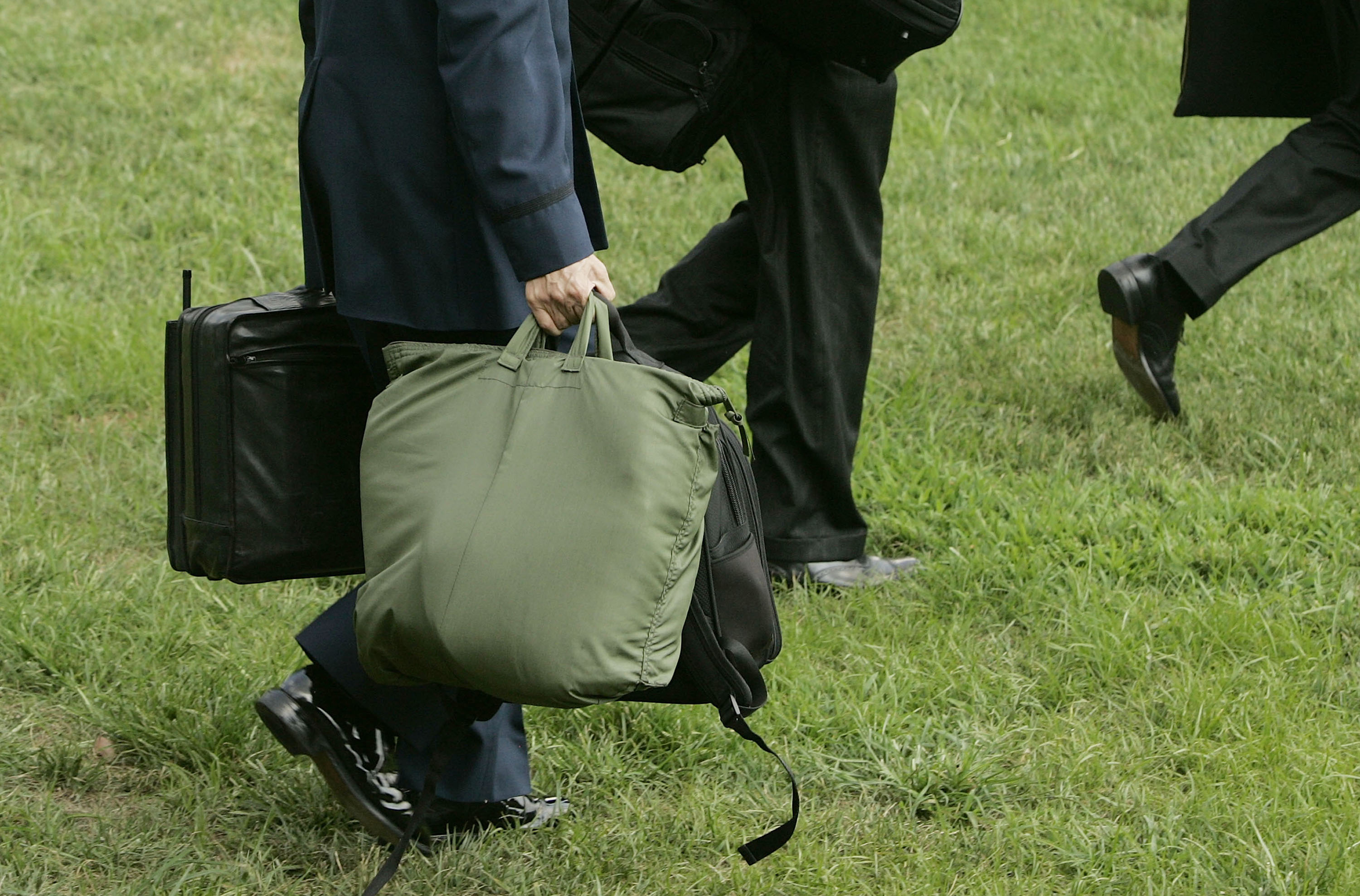 """A member of the U.S. military carries the """"football,"""" the case in his left hand, as he walks behind U.S. President George W. Bush toward Marine One on the South Lawn of the White House August 2, 2005 in Washington, DC. Photo by Mark Wilson/Getty Images"""
