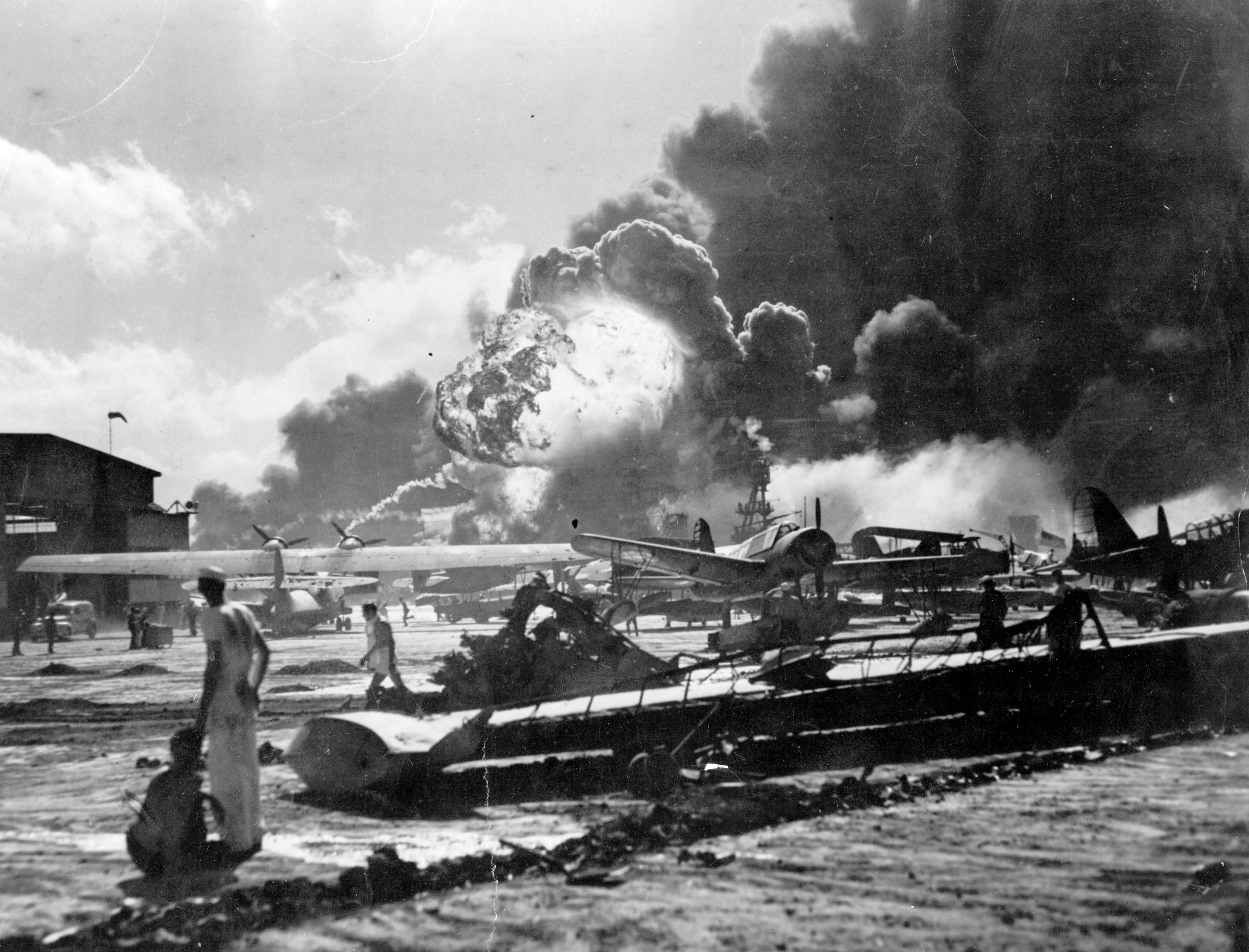 An explosion at the Naval Air Station, Ford Island, Pearl Harbour (Pearl Harbor) during the Japanese attack. Sailors stand amid wrecked watching as the USS Shaw explodes in the center background. The USS Nevada is also visible in the middle background, with her bow headed toward the left.     Photo by Fox Photos/Getty Images