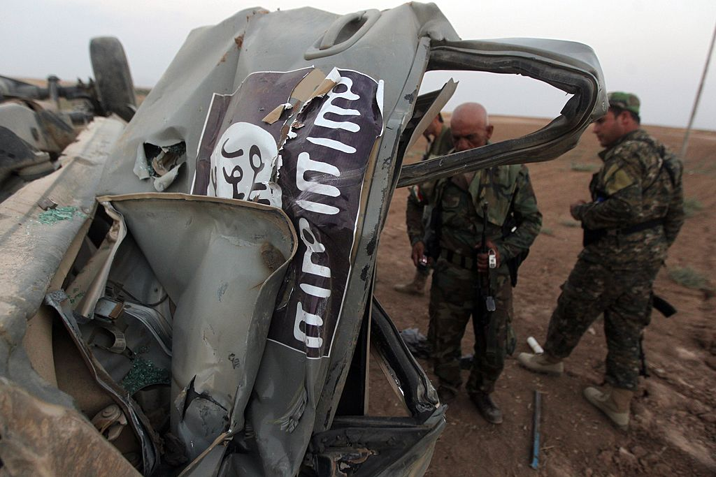 Peshmerga fighters inspect the remains of a car, bearing an image of the trademark jihadist flag, which belonged to Islamic State (IS) militants after it was targeted by an American air strike in the village of Baqufa, north of Mosul, on August 18,2014. Kurdish peshmerga fighters backed by federal forces and US warplanes pressed a counter-offensive Monday against jihadists after retaking Iraq's largest dam, as the United States and Britain stepped up their military involvement.  Photo Credit: AHMAD AL-RUBAYE/AFP/Getty Images