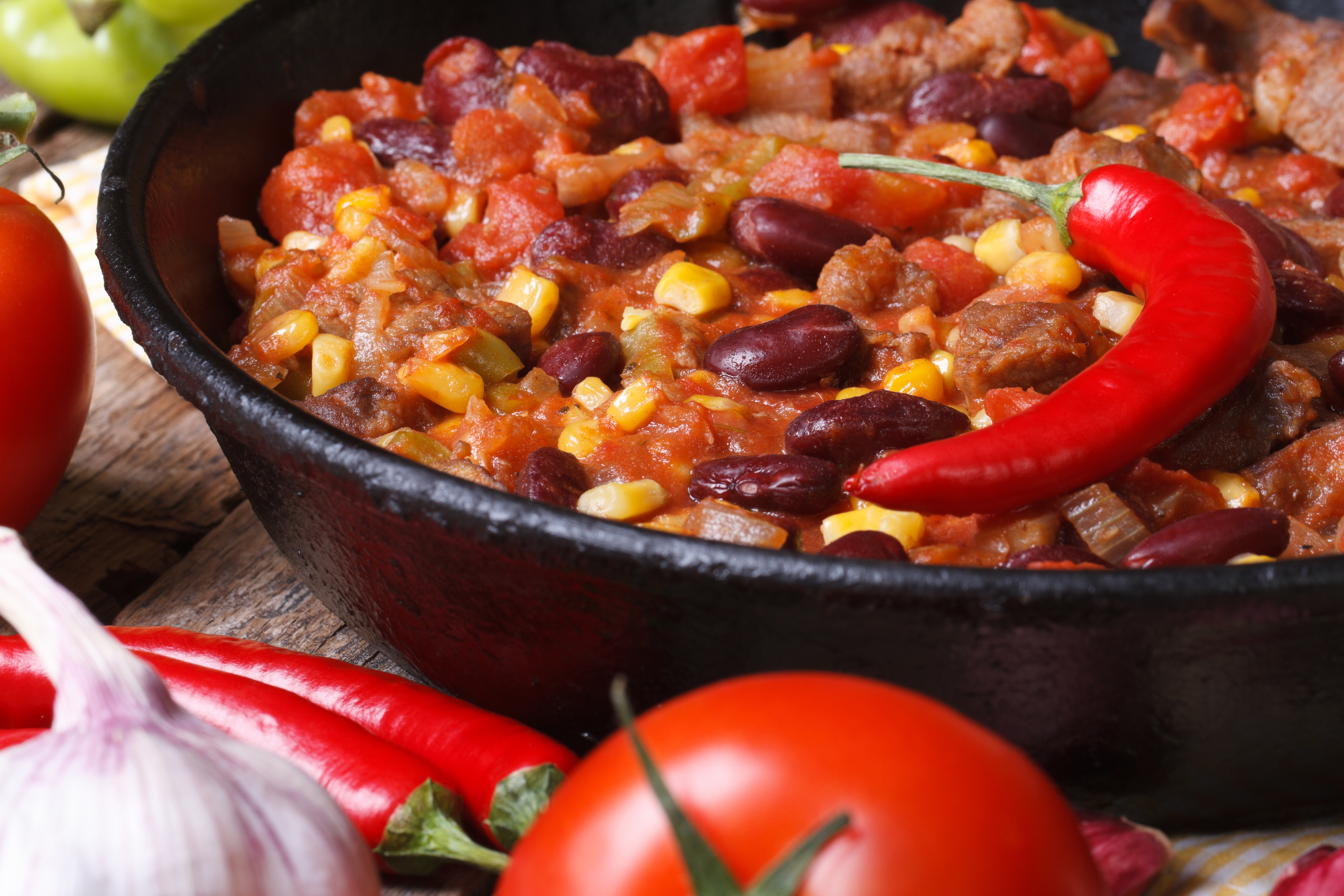 Mexican chili con carne in a pan on a wooden