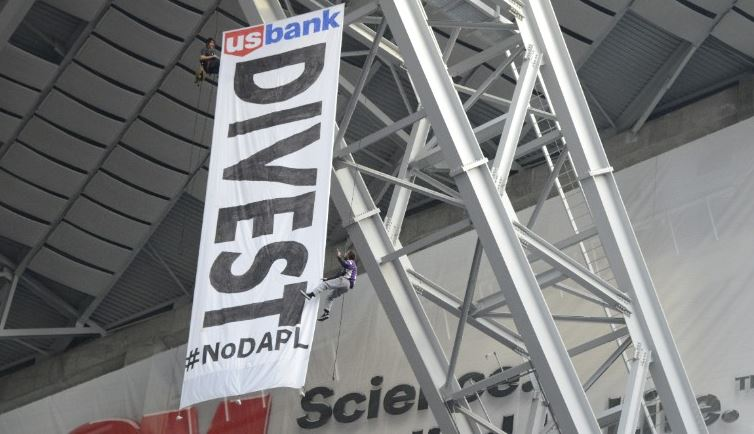 Protesters of the Dakota Access Pipeline unfurl a banner during Sunday's Minnesota Vikings game.