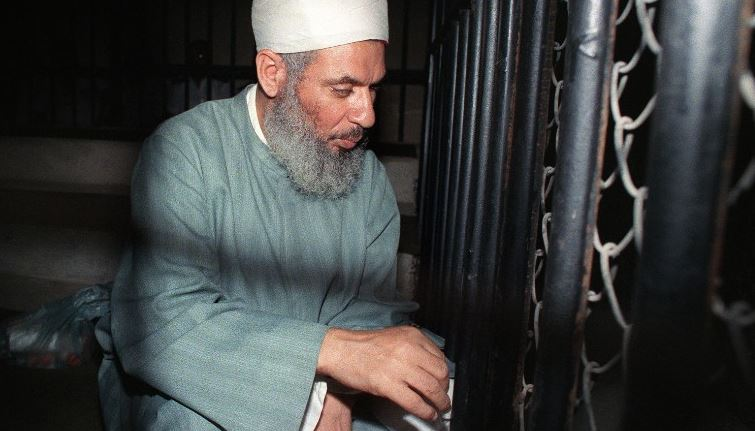 Blind Sheikh Omar Abdel-Rahmen prays inside an iron cage at the opening of court session in Aug. 1989 in Cairo.  (Getty Images)