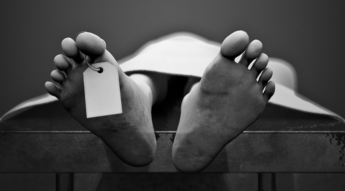 Black and white photo of a dead man's feet with toe tag