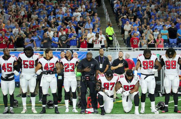 Members of the Atlanta Falcons football team take a knee during the playing of the national anthem prior to the start of the game against the Detroit Lions at Ford Field on September 24, 2017 in Detroit, MI. (Getty Images).
