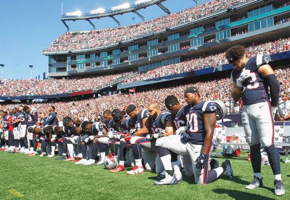 Members of the NE Patriots kneel during the National Anthem before a game against the Houston Texans at Gillette Stadium on September 24, 2017 in Foxboro, Mass. (Getty Images).