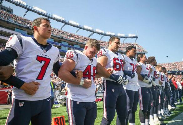 Houston Texans link arms along the sideline as the National Anthem is played before a game against the New England Patriots at Gillette Stadium on September 24, 2017 in Foxboro, Mass. (Getty Images).