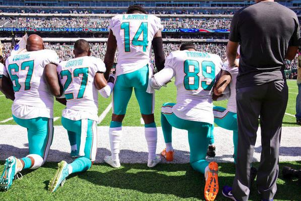 Laremy Tunsil #67, Maurice Smith #27 and Julius Thomas #89 kneel with Jarvis Landry #14 of the Miami Dolphins during the National Anthem prior to an NFL game against the NY Jets at MetLife Stadium on September 24, 2017 in East Rutherford, NJ/ (Getty Images).