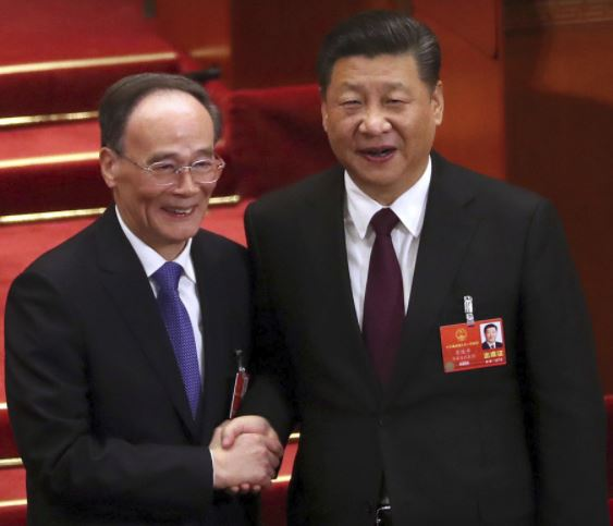 Chinese President Xi, shakes hands with Wang Qishan. Xi Jinping has been reappointed as China's president with no term limits