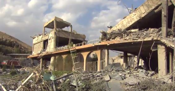 Scientist Gives Tour Of Smoldering Site Of Missile Strike In Syria Fort