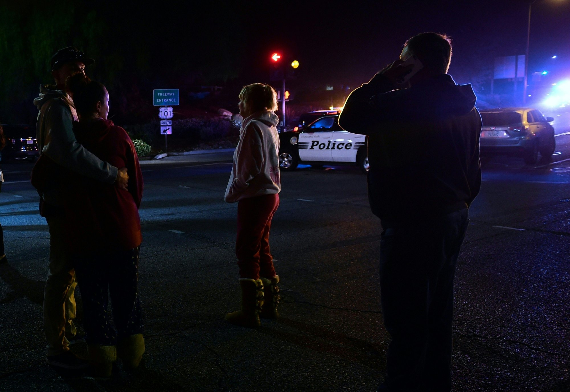 People stand and watch as the scene unfurls from the intersection of US 101 freeway and the Moorpark Rad exit as police vehicles close off the area outside a country music bar and dance hall in Thousand Oaks, west of Los Angeles, where a gunman opened fire late November 7, 2018, killing at least 12 people, US police said. (Photo by Frederic J. BROWN / AFP)        (Photo credit should read FREDERIC J. BROWN/AFP/Getty Images)