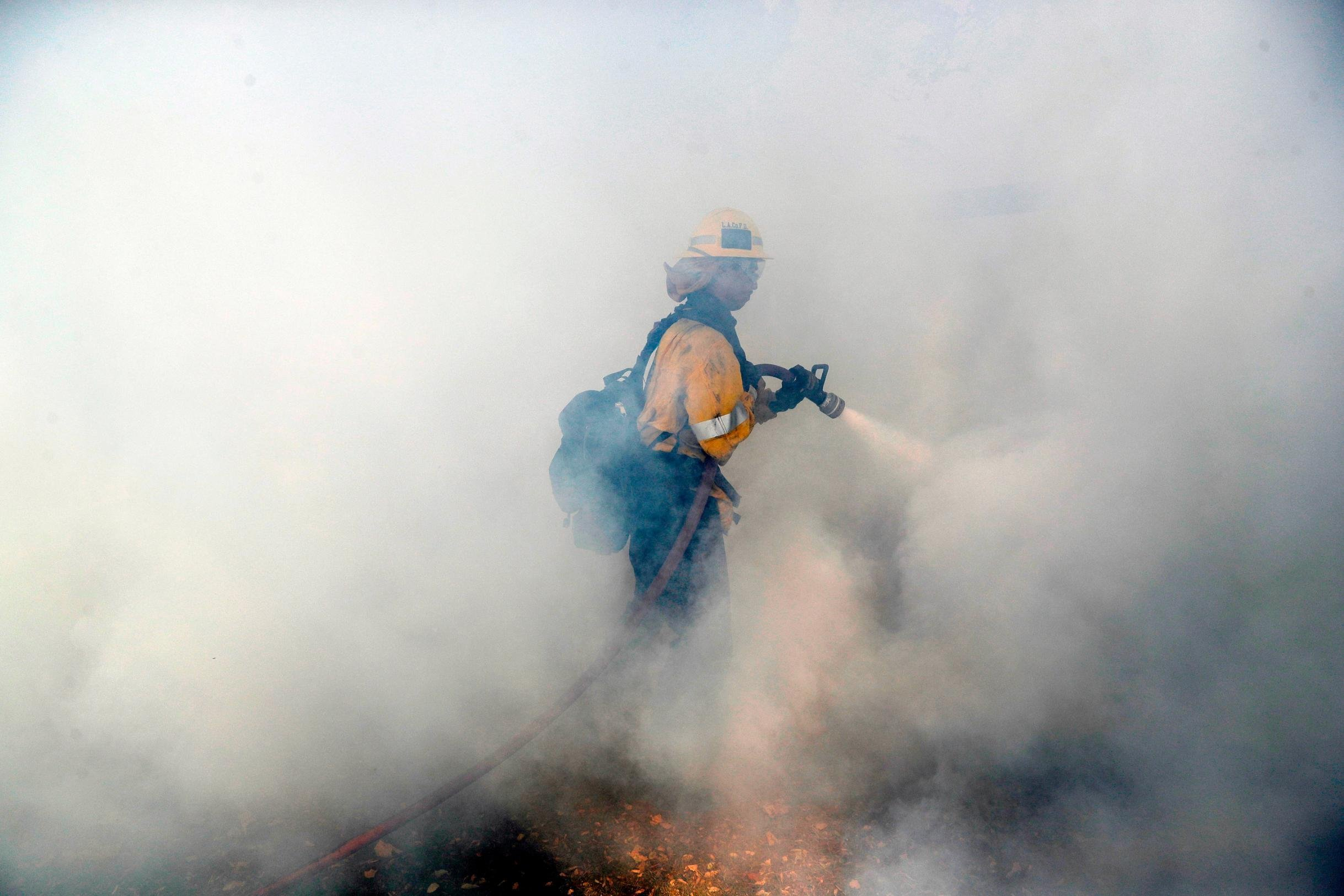 A firefighters battles a wildfire Friday in Agoura Hills in Los Angeles Count