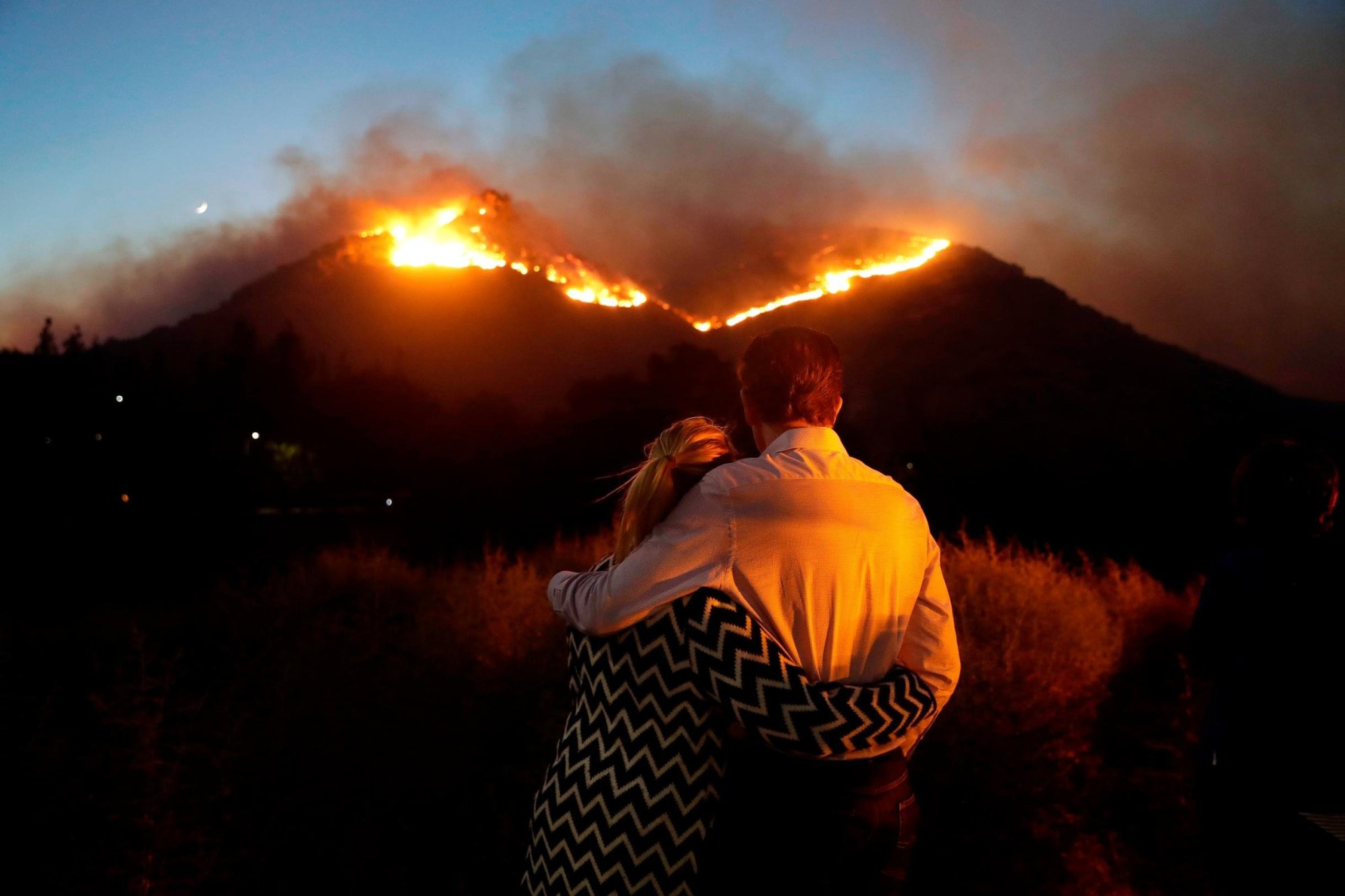Roger Bloxberg and his wife, Anne, hug as they watch a wildfire on a hilltop on Friday, November 9, near their home in the West Hills area of Los Angele
