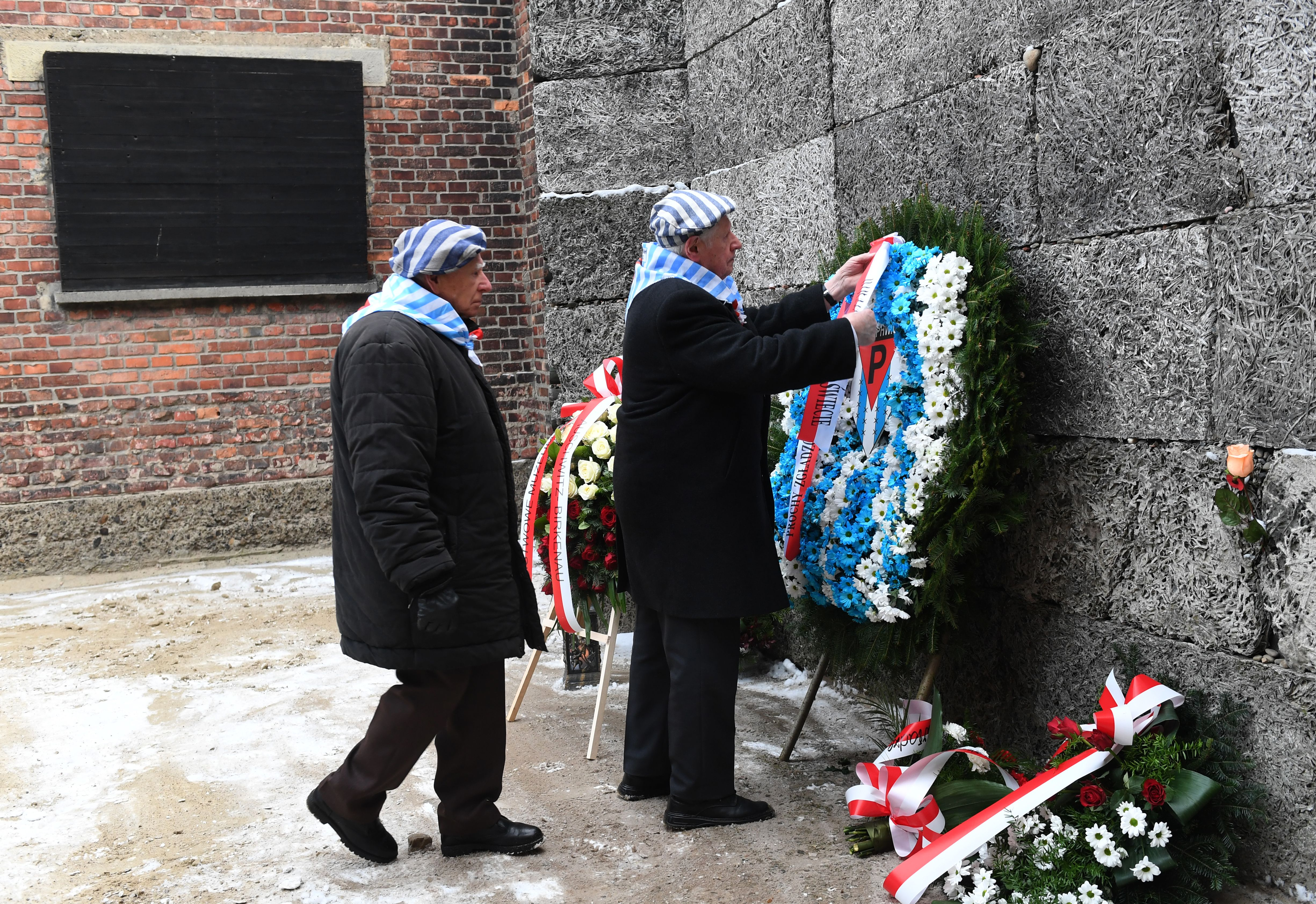 Former prisoners lay a wreath at the Death Wall marking the 74th anniversary of the liberation of former German Nazi death camp Auschwitz-Birkenau, in Oswiecim, Poland, on January 27, 2019. (Photo by Janek SKARZYNSKI / AFP)        (Photo credit should read JANEK SKARZYNSKI/AFP/Getty Images)