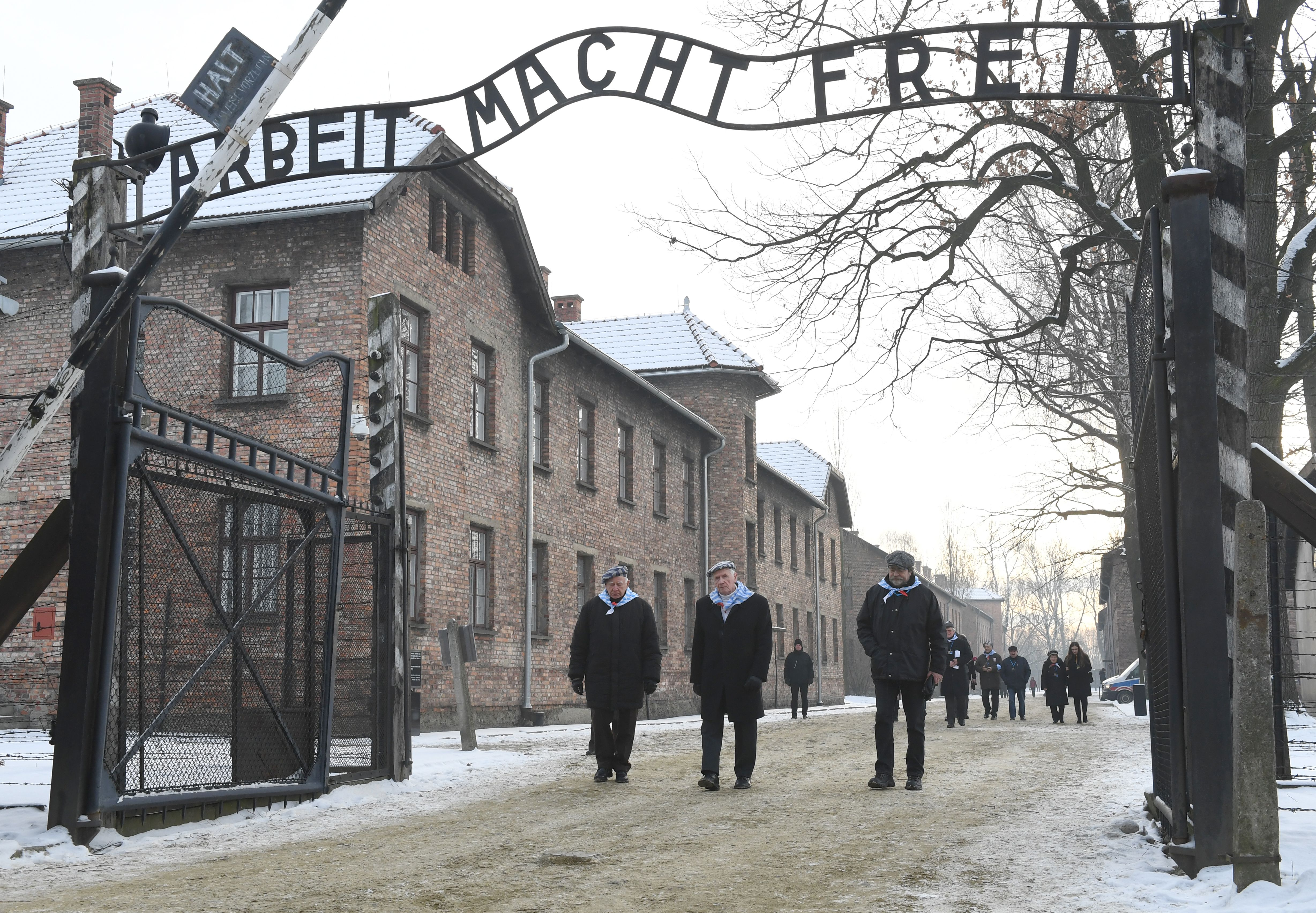 People pass the main gate after the 74th anniversary of the liberation of former German Nazi death camp Auschwitz-Birkenau, in Oswiecim, Poland, on January 27, 2019. (Photo by Janek SKARZYNSKI / AFP)        (Photo credit should read JANEK SKARZYNSKI/AFP/Getty Images)