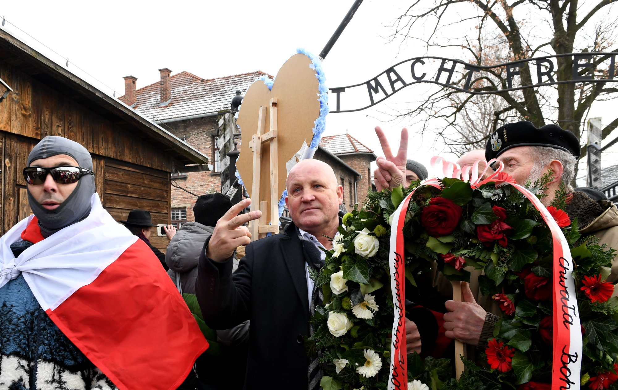 Polish far-right activist Piotr Rybak (C) and supporters gather at the main gate to the former German Nazi death camp Auschwitz-Birkenau, in Oswiecim, Poland, on January 27, 2019. - Rybak protests against the Polish government for remembering only the Jewish prisoners but not the Polish victims. (Photo by Janek SKARZYNSKI / AFP)        (Photo credit should read JANEK SKARZYNSKI/AFP/Getty Images)