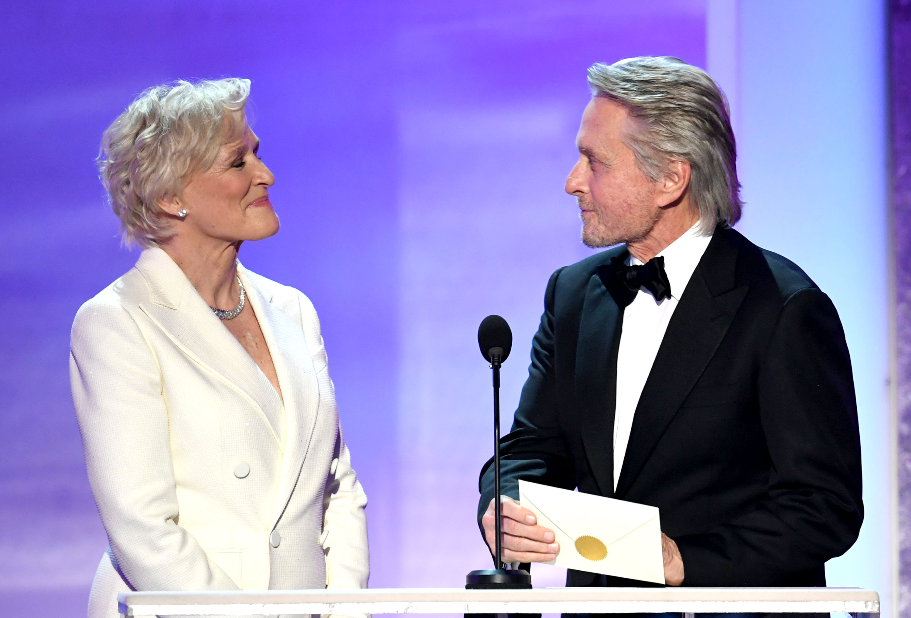 "LOS ANGELES, CALIFORNIA - JANUARY 27: Glenn Close and Michael Douglas speak onstage during the 25th Annual Screen Actors Guild Awards at The Shrine Auditorium on January 27, 2019 in Los Angeles, California. The presentation served as a reunion of sorts for the ""Fatal Attraction"" stars, the 1987 movie that solidified stardom for both. (Photo by Kevin Winter/Getty Images for Turner)"