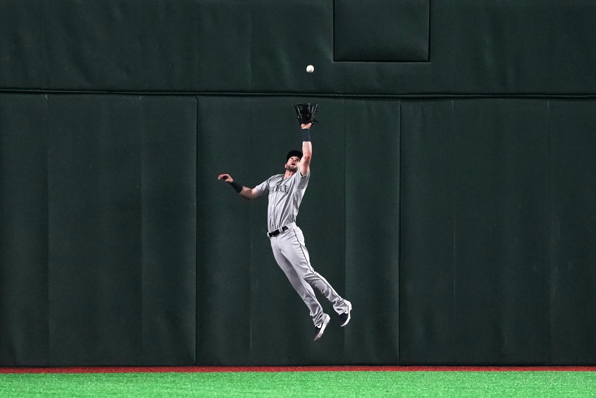 TOKYO, JAPAN - MARCH 20: Outfielder Mitch Haniger #17 of the Seattle Mariners leaps for a fly by Outfielder Stephen Piscotty #25 of the Oakland Athletics in the 7th inning during the game between Seattle Mariners and Oakland Athletics at Tokyo Dome on March 20, 2019 in Tokyo, Japan. (Photo by Masterpress/Getty Images)
