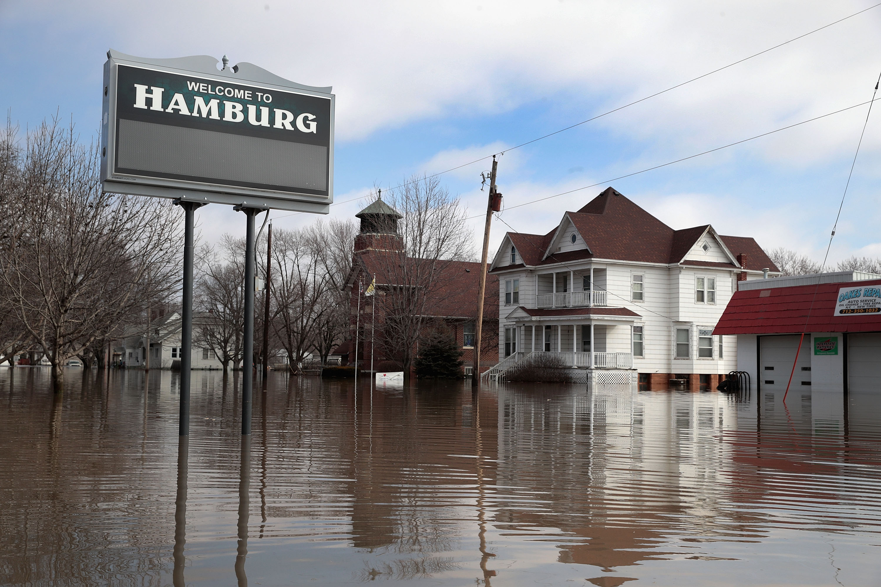 """HAMBURG, IOWA - MARCH 20:  A home sits in flood water on March 20, 2019 in Hamburg, Iowa. Although flood water in the town has started to recede many homes and businesses remain surrounded by water. Several Midwest states are battling some of the worst flooding they have experienced in decades as rain and snow melt from the recent """"bomb cyclone"""" has inundated rivers and streams. At least three deaths have been linked to the flooding.  (Photo by Scott Olson/Getty Images)"""