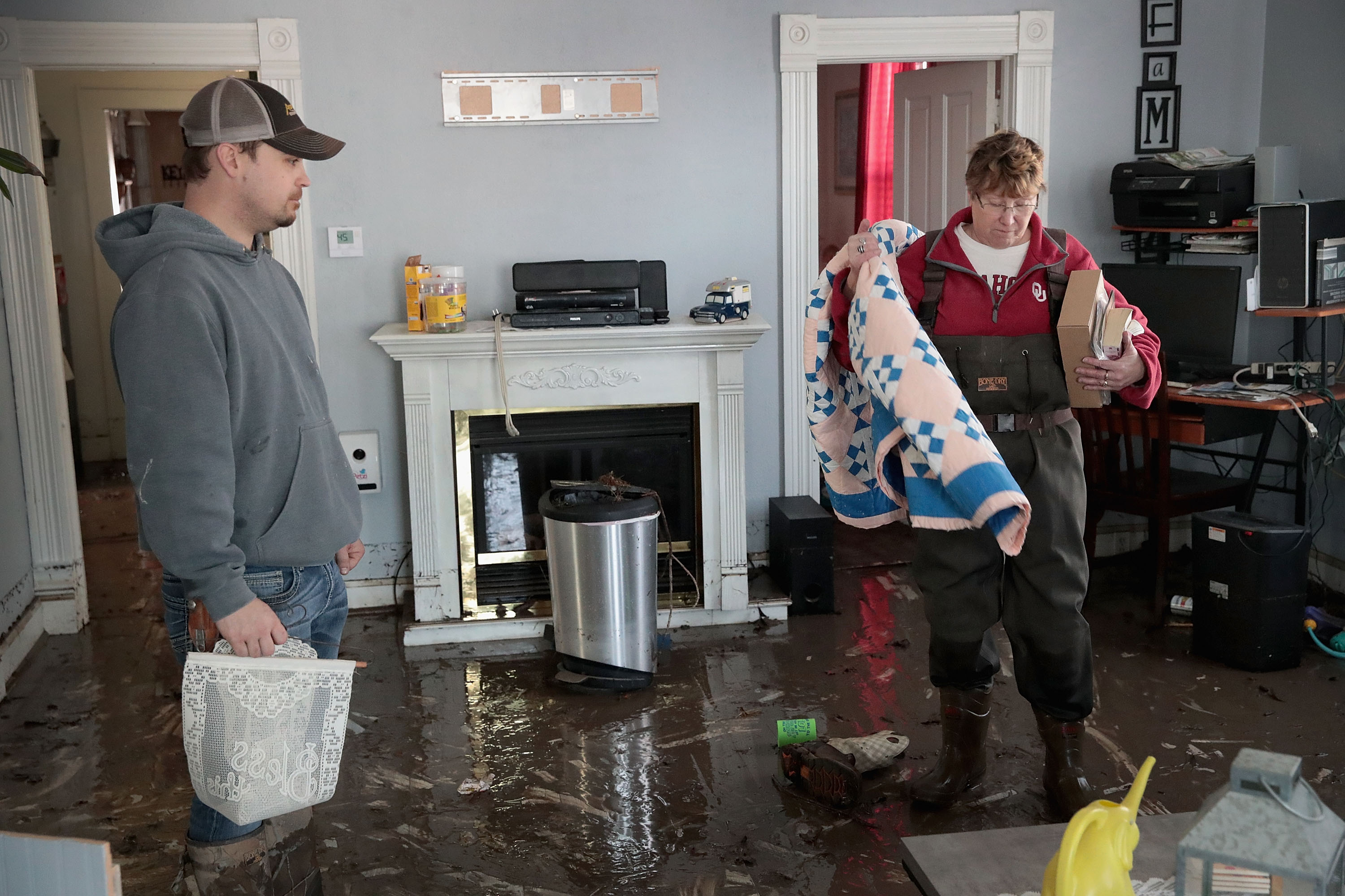 """HAMBURG, IOWA - MARCH 20:  Joey Peeler (L) helps his friend Kathy Drummond remove items from her flooded home on March 20, 2019 in Hamburg, Iowa. Although flood water in the town has started to recede many homes and businesses remain surrounded by water. Several Midwest states are battling some of the worst flooding they have experienced in decades as rain and snow melt from the recent """"bomb cyclone"""" has inundated rivers and streams. At least three deaths have been linked to the flooding.  (Photo by Scott Olson/Getty Images)"""