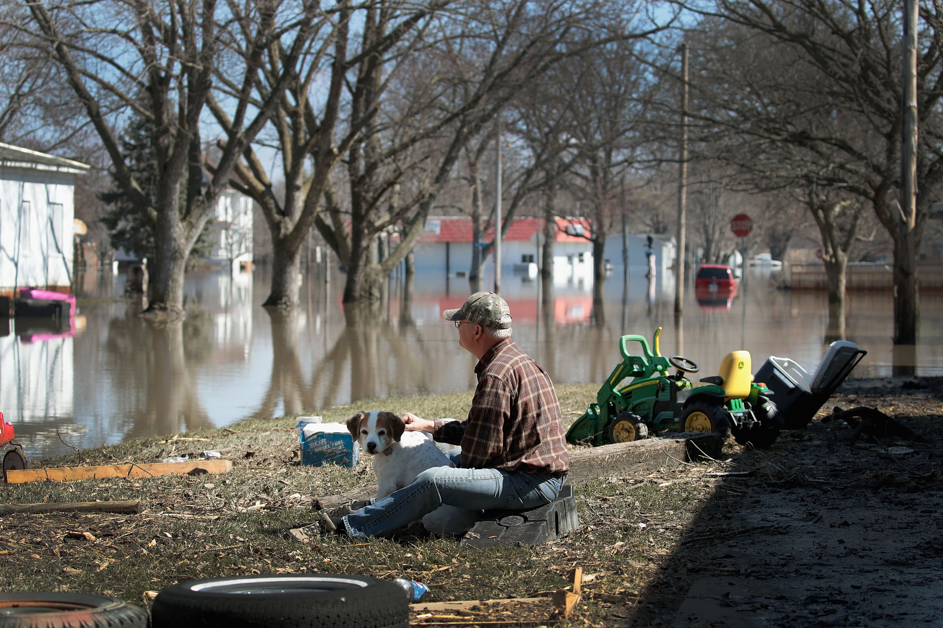 """HAMBURG, IOWA - MARCH 20:  Dave Mincer sits along a flooded street with a friend's dog on March 20, 2019 in Hamburg, Iowa. Although flood water in the town has started to recede many homes and businesses remain surrounded by water. Several Midwest states are battling some of the worst flooding they have experienced in decades as rain and snow melt from the recent """"bomb cyclone"""" has inundated rivers and streams. At least three deaths have been linked to the flooding.  (Photo by Scott Olson/Getty Images)"""