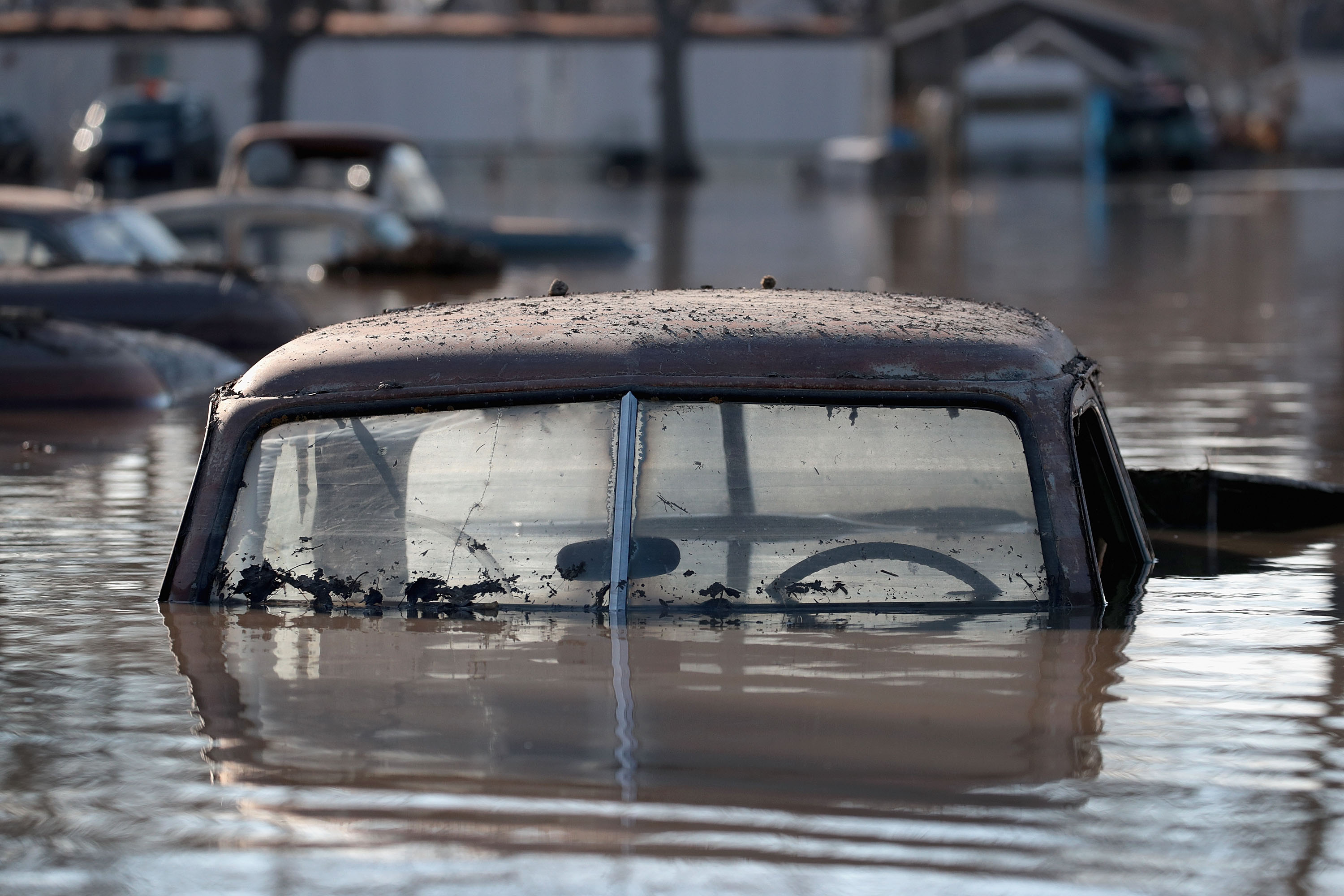 """HAMBURG, IOWA - MARCH 20:  A vintage car sits in flood water on March 20, 2019 in Hamburg, Iowa. Although flood water in the town has started to recede many homes and businesses remain surrounded by water. Several Midwest states are battling some of the worst flooding they have experienced in decades as rain and snow melt from the recent """"bomb cyclone"""" has inundated rivers and streams. At least three deaths have been linked to the flooding. (Photo by Scott Olson/Getty Images)"""