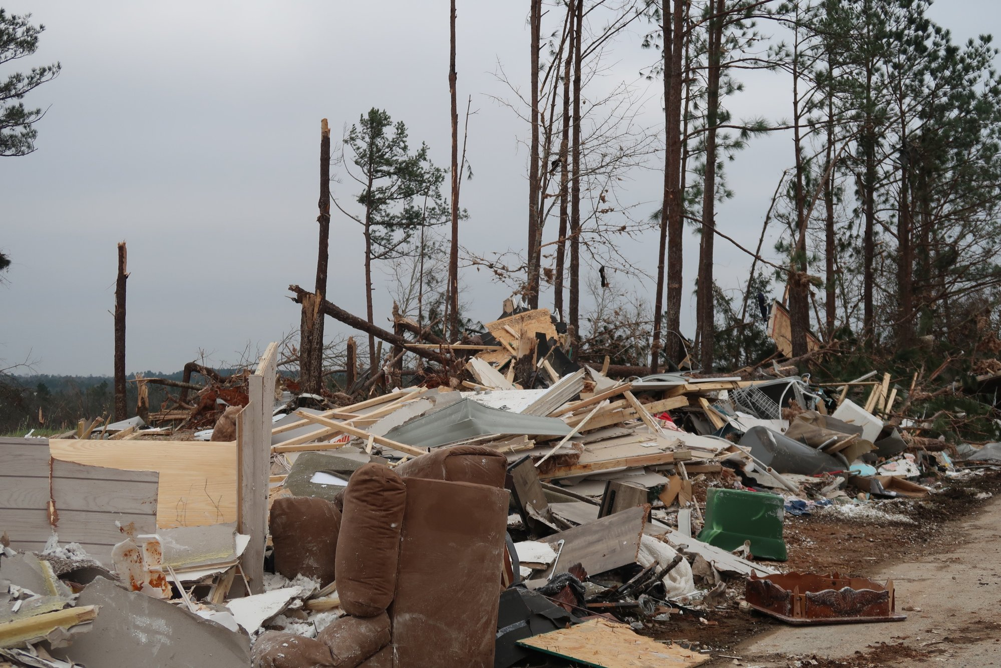 Yellow insulation is seen strewn across trees and debris and bricks that were once the foundation for mobile homes are scattered everywhere.