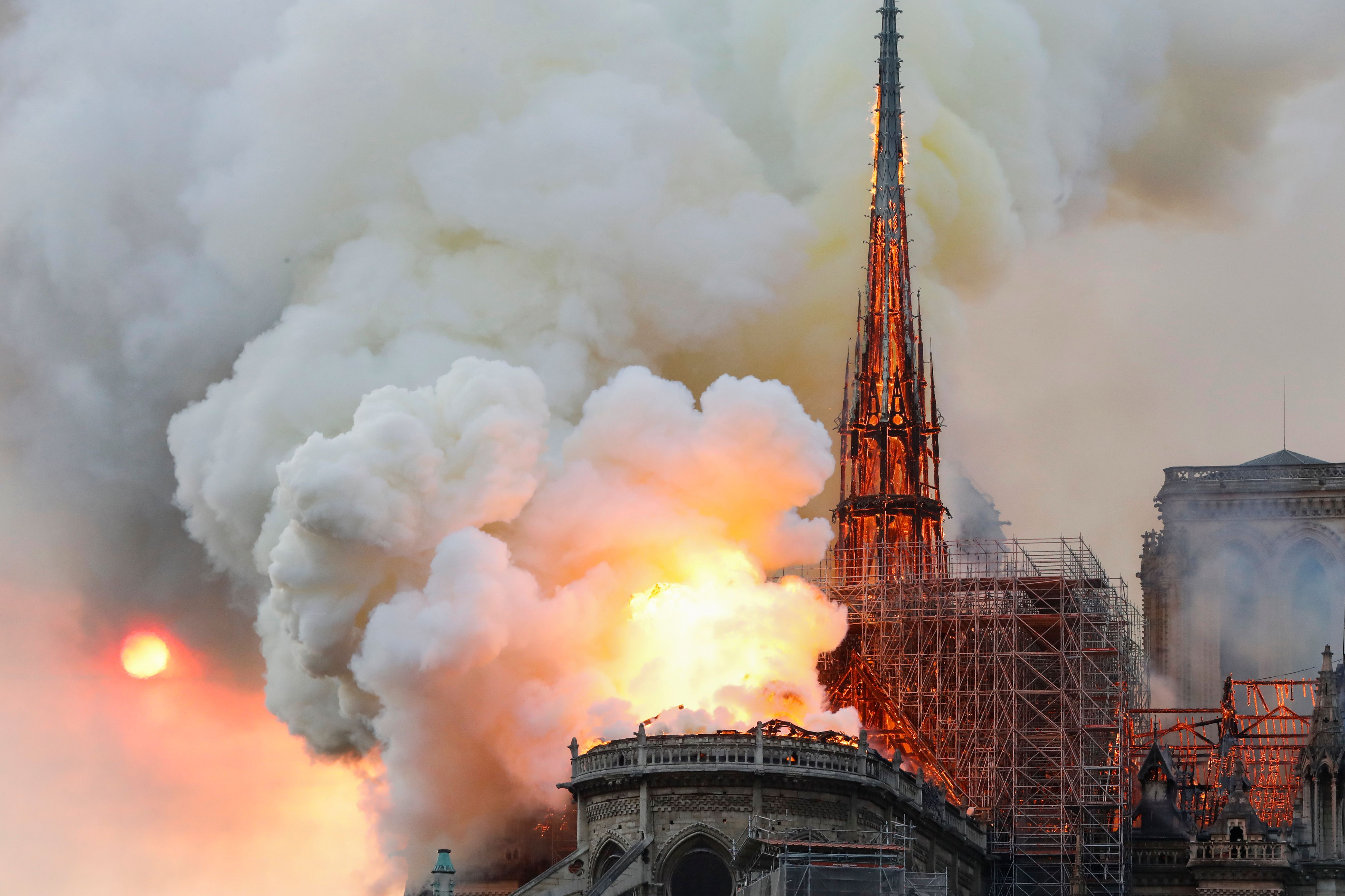 TOPSHOT - Smoke and flames rise during a fire at the landmark Notre-Dame Cathedral in central Paris on April 15, 2019, potentially involving renovation works being carried out at the site, the fire service said. - A major fire broke out at the landmark Notre-Dame Cathedral in central Paris sending flames and huge clouds of grey smoke billowing into the sky, the fire service said. The flames and smoke plumed from the spire and roof of the gothic cathedral, visited by millions of people a year, where renovations are currently underway. (Photo by FRANCOIS GUILLOT / AFP)        (Photo credit should read FRANCOIS GUILLOT/AFP/Getty Images)