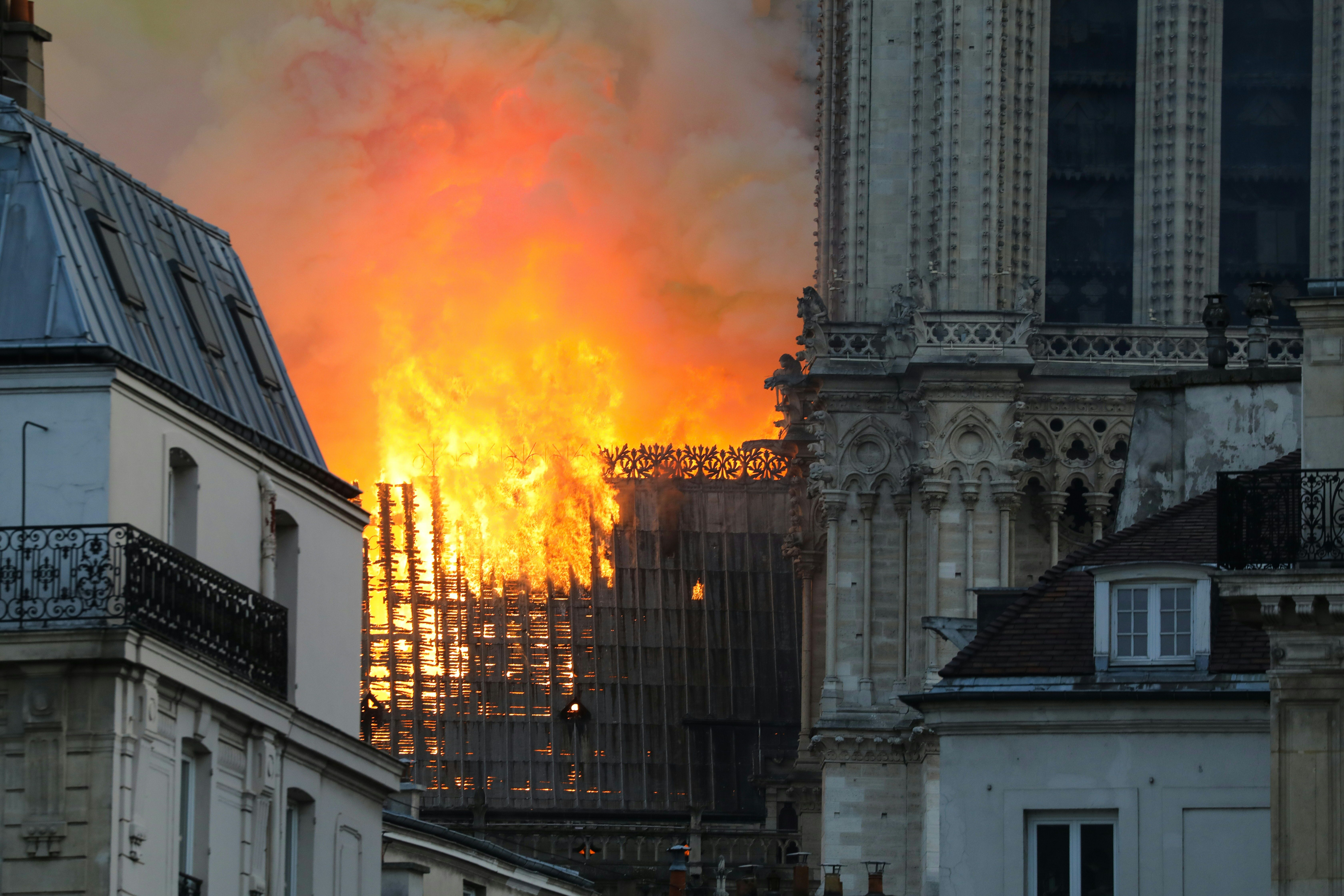 Smoke and flames rise during a fire at the landmark Notre-Dame Cathedral in central Paris on April 15, 2019, potentially involving renovation works being carried out at the site, the fire service said. - A major fire broke out at the landmark Notre-Dame Cathedral in central Paris sending flames and huge clouds of grey smoke billowing into the sky, the fire service said. The flames and smoke plumed from the spire and roof of the gothic cathedral, visited by millions of people a year, where renovations are currently underway. (Photo by LUDOVIC MARIN / AFP)        (Photo credit should read LUDOVIC MARIN/AFP/Getty Images)